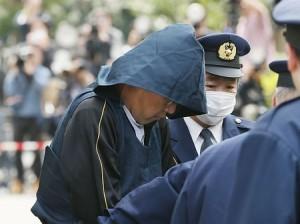 Nghi phạm sát hại bé Nhật Linh xuất hiện trong chiếc khăn trùm đầu, mặt cúi gằm, tránh ống kính của phóng viên